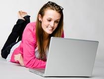 Giovane donna attraente che si distende con il computer portatile Immagini Stock