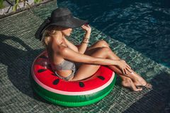 giovane donna attraente che si siede in anello gonfiabile al poolside immagini stock libere da diritti