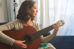 Giovane donna attraente che si siede a casa giocando la chitarra spagnola fotografia stock libera da diritti