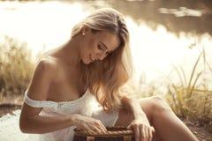 Giovane donna attraente che si siede dal lago al tramonto e che tiene il canestro di picnic fotografia stock libera da diritti
