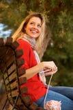 Giovane donna attraente che si siede fuori del tricottare sciarpa fotografia stock libera da diritti