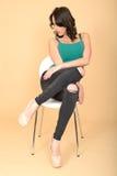 Giovane donna attraente che si siede su una sedia in scarpe del tacco alto e Immagine Stock