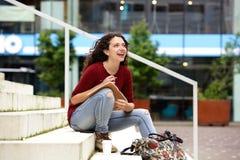 Giovane donna attraente che si siede sui punti con il taccuino e sorridere Fotografia Stock