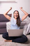 Giovane donna attraente che si siede sul pavimento che guarda in avanti alla h Fotografia Stock