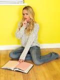 Giovane donna attraente che si siede sul pavimento che legge un libro Fotografia Stock Libera da Diritti