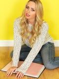 Giovane donna attraente che si siede sul pavimento che legge un libro Fotografia Stock
