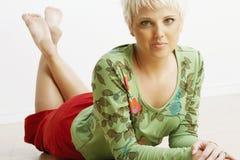 Giovane donna attraente che si trova giù Immagini Stock Libere da Diritti