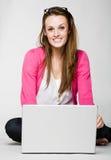 Giovane donna attraente che sorride con il computer portatile Immagini Stock