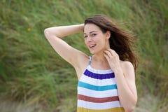Giovane donna attraente che sorride con la mano in capelli Immagine Stock