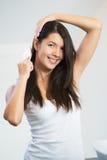 Giovane donna attraente che spazzola i suoi capelli lunghi Immagine Stock Libera da Diritti