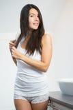 Giovane donna attraente che spazzola i suoi capelli lunghi Fotografia Stock Libera da Diritti