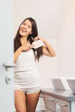 Giovane donna attraente che spazzola i suoi capelli lunghi Immagini Stock Libere da Diritti