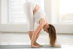 Giovane donna attraente che sta nella posa di uttanasana, colore bianco fotografie stock libere da diritti