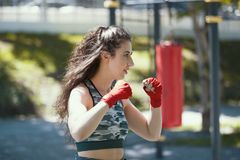 Giovane donna attraente che sta in una posizione del pugile, allenamento nel parco di estate Immagini Stock Libere da Diritti