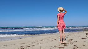 Giovane donna attraente che tiene il suo cappello e che porta vestito rosso che esamina il mare e l'orizzonte tempestosi Il vesti archivi video