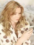 Giovane donna attraente che tiene un telefono cellulare del telefono cellulare di Smartphone Fotografie Stock