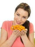 Giovane donna attraente che tiene una manciata di anello condito cipolla Fotografia Stock
