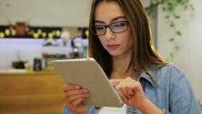 Giovane donna attraente che utilizza il touch screen della compressa e nel caffè moderno video d archivio