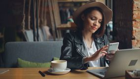 Giovane donna attraente che utilizza smartphone nel caffè che gode del sorridere sociale di media video d archivio