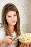 Giovane donna attraente che wathcing TV e che tiene schiocco Immagine Stock Libera da Diritti