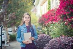 Giovane donna attraente con i libri in via soleggiata Immagini Stock