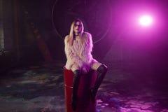 Giovane donna attraente con i vestiti alla moda La bella ragazza in pelliccia rosa lanuginosa si siede sul barilotto Luce al neon Fotografie Stock Libere da Diritti
