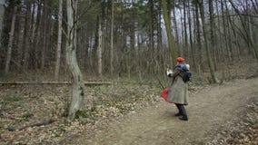 Giovane donna attraente con il cappello rosso che fila intorno foresta stock footage