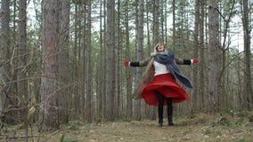 Giovane donna attraente con il cappello rosso che fila intorno foresta video d archivio