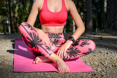 Giovane donna attraente con l'orologio astuto che prende una rottura dopo l'allenamento di yoga Sport, forma fisica, allenamento Fotografia Stock