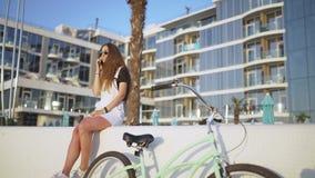 Giovane donna attraente con la bicicletta che parla sul telefono vicino all'hotel in mare alba o tramonto video d archivio