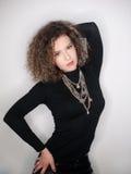 Giovane donna attraente con la blusa nera del collo alto contro la parete bianca Ragazza sveglia con capelli ricci lunghi in attr Fotografia Stock Libera da Diritti