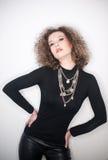 Giovane donna attraente con la blusa nera del collo alto contro la parete bianca Ragazza sveglia con capelli ricci lunghi in attr Fotografie Stock