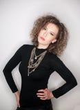Giovane donna attraente con la blusa nera del collo alto contro la parete bianca Ragazza sveglia con capelli ricci lunghi in attr Immagine Stock