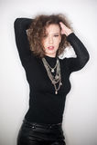 Giovane donna attraente con la blusa nera del collo alto contro la parete bianca Ragazza sveglia con capelli ricci lunghi in attr Immagine Stock Libera da Diritti