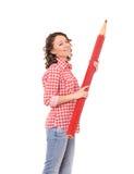 Giovane donna attraente con la matita rossa enorme Fotografia Stock