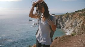 Giovane donna attraente con le passeggiate dei capelli e dello zaino di volo al punto di stupore di vista dell'oceano di estate a archivi video