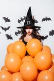 Giovane donna attraente in costume di Halloween della strega con i palloni arancio Fotografia Stock Libera da Diritti