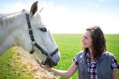 Giovane donna attraente dell'agricoltore che parla con cavallo Immagini Stock Libere da Diritti