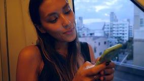 Giovane donna attraente della corsa mista che guida una metropolitana della metropolitana e che manda un sms sul telefono cellula archivi video