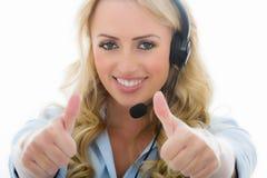 Giovane donna attraente di affari che per mezzo di una cuffia avricolare del telefono Fotografie Stock Libere da Diritti