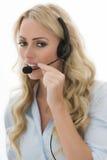 Giovane donna attraente di affari che per mezzo di una cuffia avricolare del telefono Immagini Stock Libere da Diritti