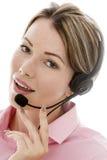 Giovane donna attraente di affari che per mezzo di una cuffia avricolare del telefono Immagini Stock
