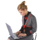 Giovane donna attraente di affari che si siede sulla presidenza e sul funzionamento della barra Fotografia Stock Libera da Diritti
