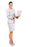 Giovane donna attraente di affari che si siede sulla presidenza e sul funzionamento della barra fotografia stock