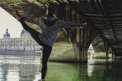 Giovane donna attraente di forma fisica che fa esercizio e che allunga le gambe nella città Architettura magnifica nei precedenti immagine stock