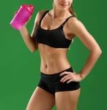 Giovane donna attraente di forma fisica con una bottiglia di sport sul BAC verde Fotografia Stock