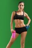 Giovane donna attraente di forma fisica con una bottiglia di sport sul BAC verde Immagine Stock