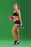 Giovane donna attraente di forma fisica con una bottiglia di sport sul BAC verde Fotografie Stock Libere da Diritti