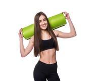 Giovane donna attraente di forma fisica pronta per l'allenamento che giudica la stuoia verde di yoga isolata su fondo bianco Fotografia Stock