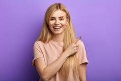 Giovane donna attraente emozionante che indica allo spazio della copia fotografie stock libere da diritti